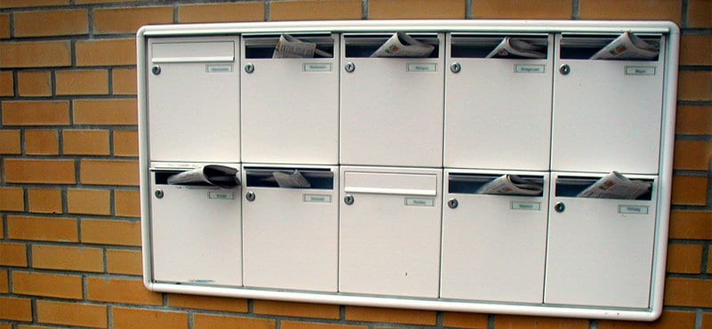 Mailboxes mounted on a wall with newspapers in them